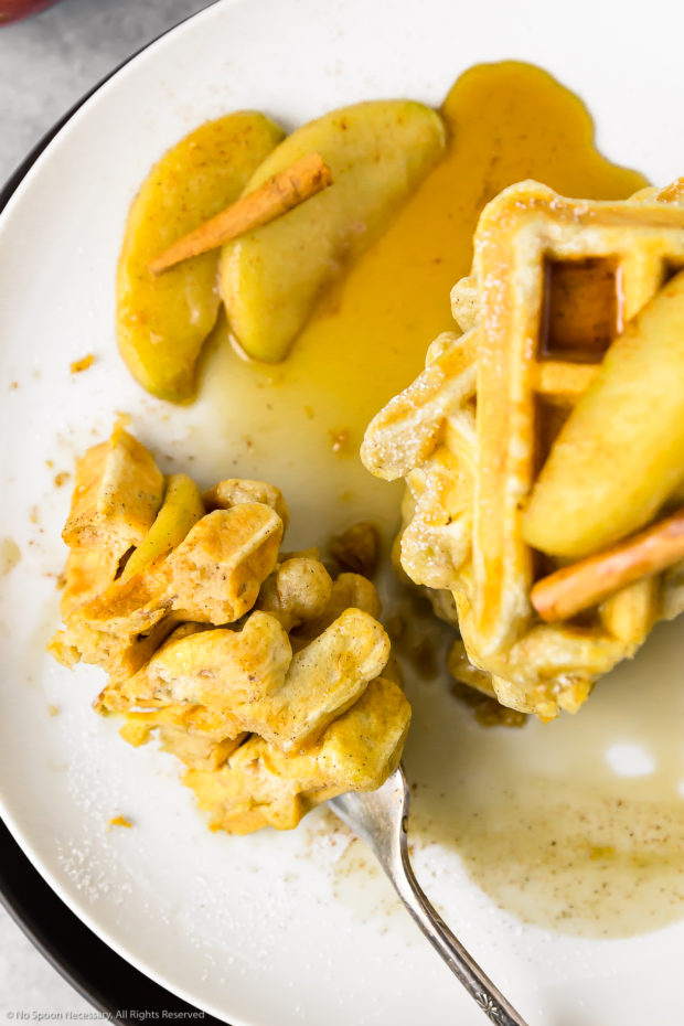 Overhead photo of a stack of Apple Cinnamon Waffles with Bourbon Maple Syrup on a white plate with a fork piercing a slice of the waffles next to the stack.