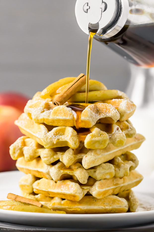 Straight on photo of a stack of Apple Cinnamon Waffles on a white plate with Maple Syrup in a glass jar being poured on top of the waffles.