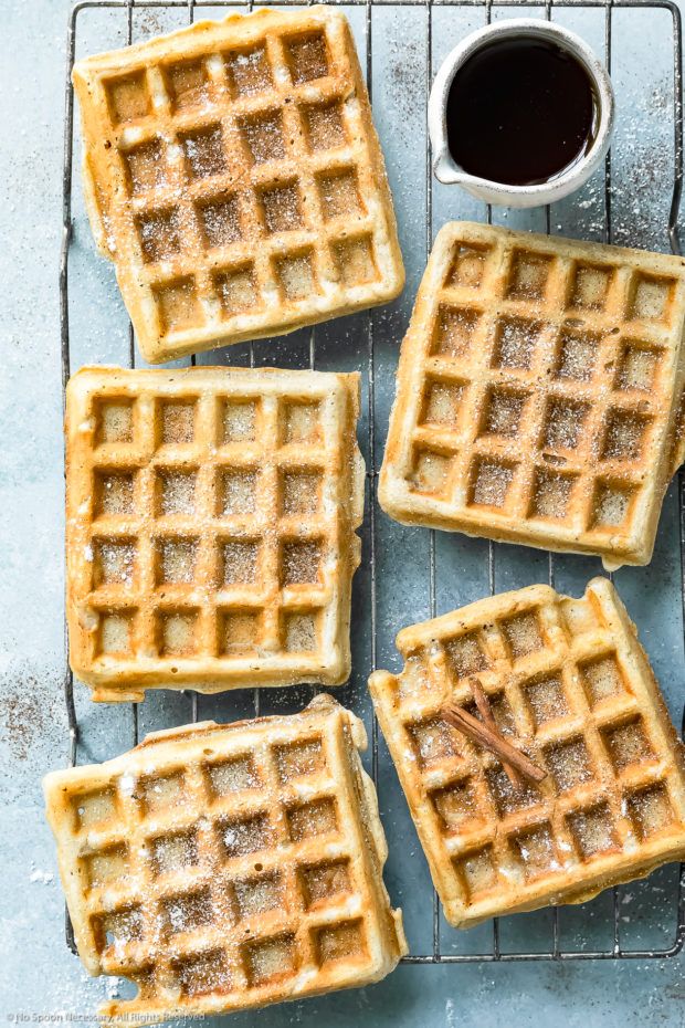 Overhead photo of Belgian cinnamon waffles dusted with powdered sugar and cinnamon on a wire cooling rack with a small ramekin of pure maple syrup off to the side.