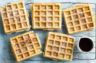 Overhead photo of Apple Cinnamon Waffles dusted with ground cinnamon and powdered sugar on a wire cooling rack with a ramekin of pure maple syrup.