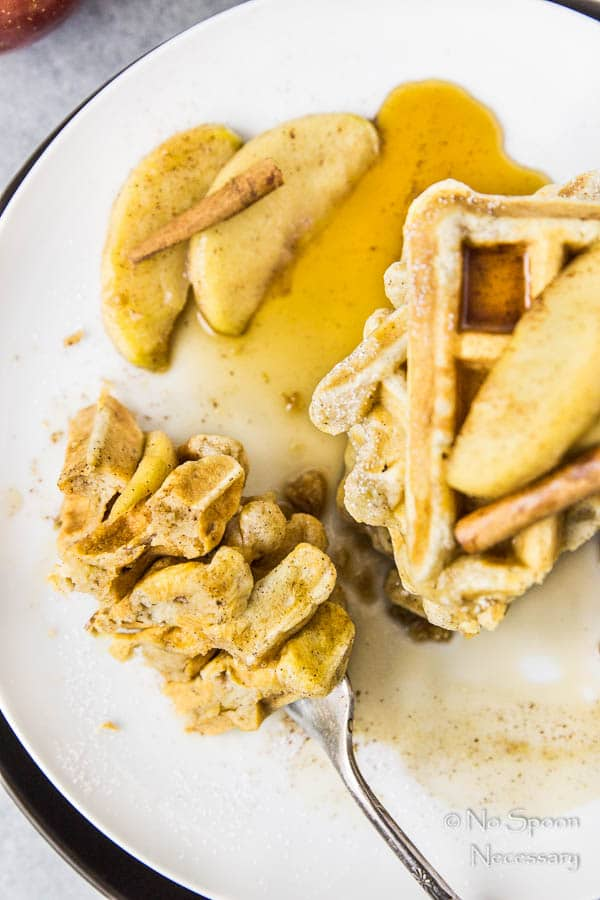Overhead shot of a stack of Apple Cinnamon Waffles with Bourbon Maple Syrup on a white plate with a fork piercing a slice of the waffles next to the stack.