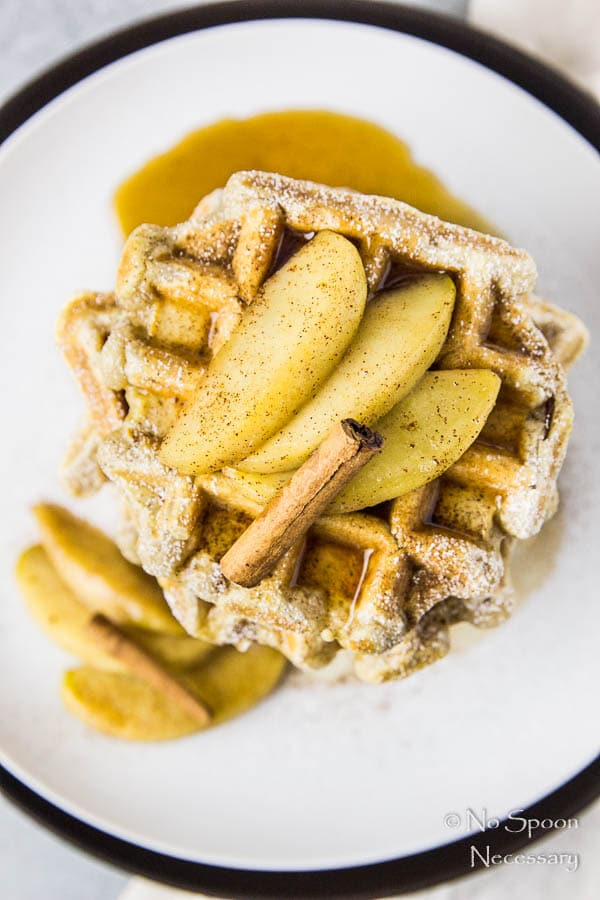 Overhead shot of a stack of Apple Cinnamon Waffles topped with Bourbon Maple Syrup, sliced apples and a cinnamon stick on a white plate.