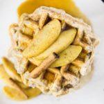 Overhead landscape shot of a stack of Apple Cinnamon Waffles topped with Bourbon Maple Syrup, sliced apples and a cinnamon stick on a white plate.