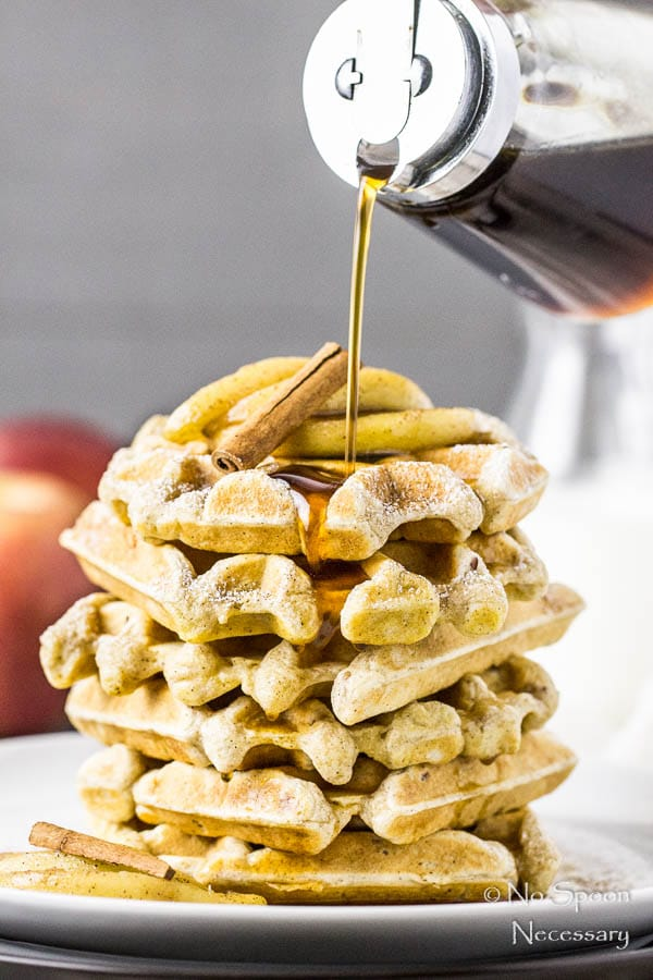 Straight on shot of a stack of Apple Cinnamon Waffles on a white plate with Bourbon Maple Syrup in a glass jar being poured on top of the waffles.