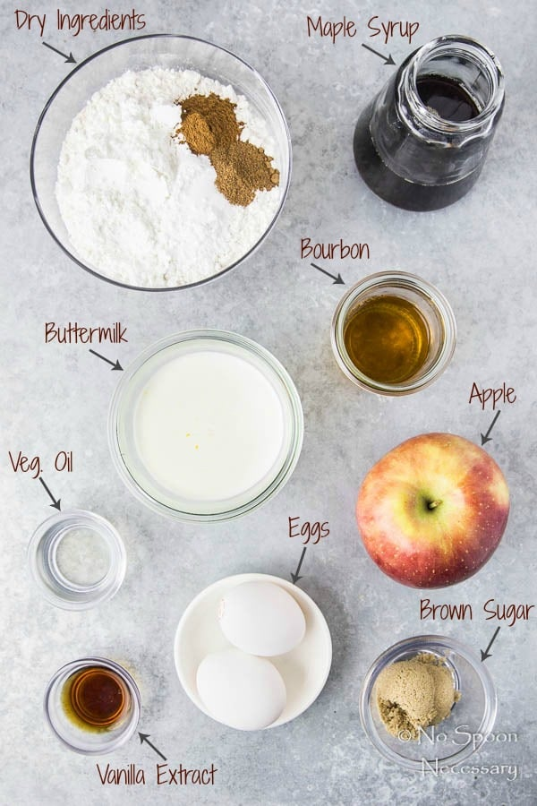 Overhead shot of the ingredients to make Apple Cinnamon Waffles with Bourbon Maple Syrup neatly organized on a gray surface.
