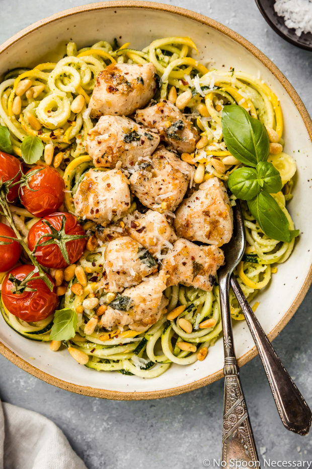 Overhead, up-close shot of Basil Garlic Chicken & Pesto Zucchini Noodles in a large bowl with oven roasted tomatoes and two forks inserted into the noodles.