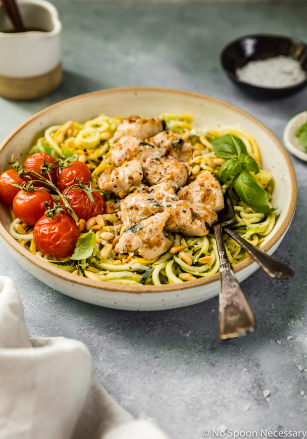 Angled shot of Basil Garlic Chicken & Pesto Zucchini Noodles in a large bowl with oven roasted tomatoes and two forks inserted into the noodles; with a small jar of pesto, neutral linen, and ramekins of salt and basil surrounding the bowl.