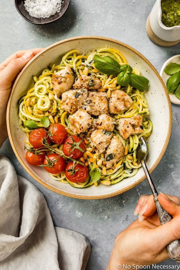 Overhead shot of Basil Garlic Chicken & Pesto Zucchini Noodles in a large bowl garnished with oven roasted tomatoes with a hand holding a fork inserted into the noodles and another hand holding the side of the bowl; with a small jar of pesto, neutral linen, and ramekins of salt and basil surrounding the bowl.