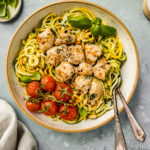 Overhead, landscape shot of Basil Garlic Chicken & Pesto Zucchini Noodles in a large bowl with oven roasted tomatoes and two forks inserted into the noodles; with a small jar of pesto, neutral linen, and ramekins of salt and basil surrounding the bowl.