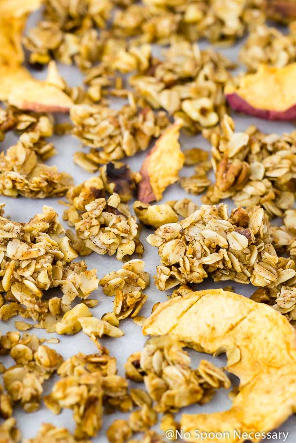 Angled up-close shot of Cinnamon Apple Pie Granola with apple chips on a piece of parchment paper