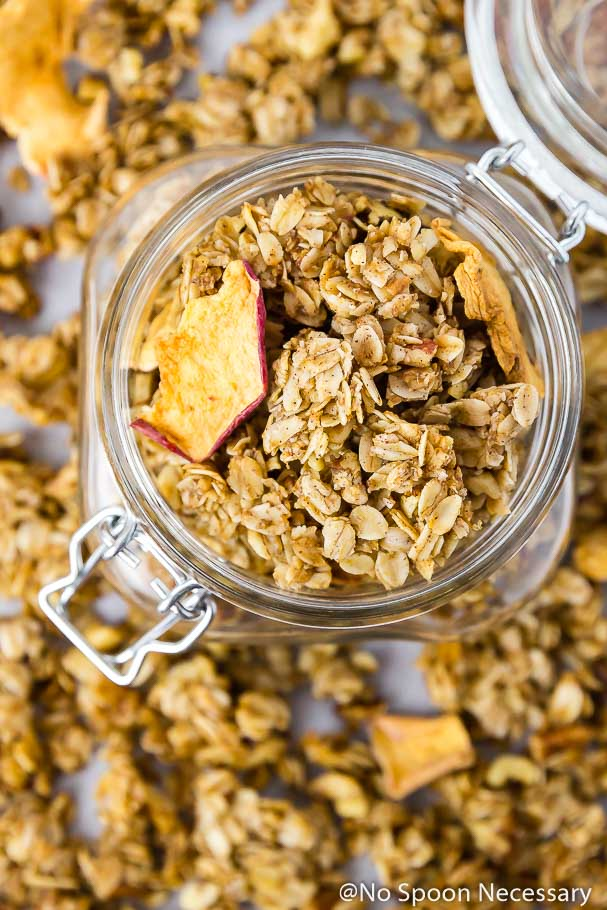 Overhead shot of a clear mason jar full of Cinnamon Apple Pie Granola with more granola blurred in the background surrounding the jar