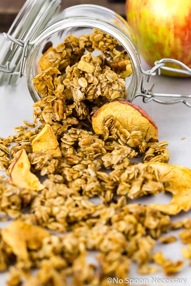 Angled shot of a mason jar filled with Cinnamon Apple Pie Granola tipped over and spilling out onto a piece of white parchment paper with an apple in the background