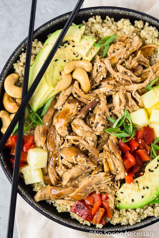 Overhead shot of Slow Cooker Chicken Teriyaki Quinoa Bowls with black chop sticks on a silver board with a neutral linen