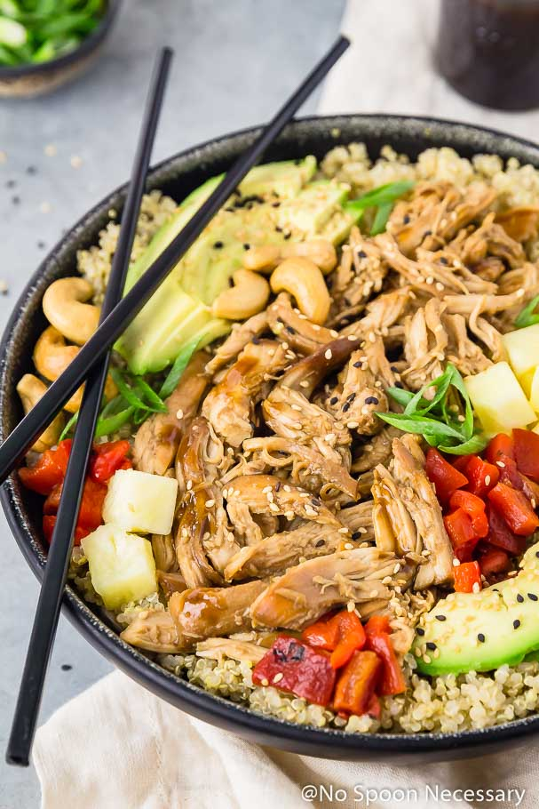 Slow cooker chicken teriyaki quinoa bowls no spoon necessary angled shot of a slow cooker chicken teriyaki quinoa bowl with black chop sticks balancing on forumfinder Choice Image