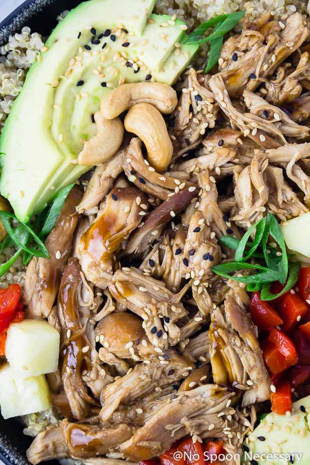 Overhead, up-close shot of Slow Cooker Chicken Teriyaki served on quinoa with slices of avocado, cashews, diced red peppers, chunks of pineapple, slices of green onion and sesame seeds