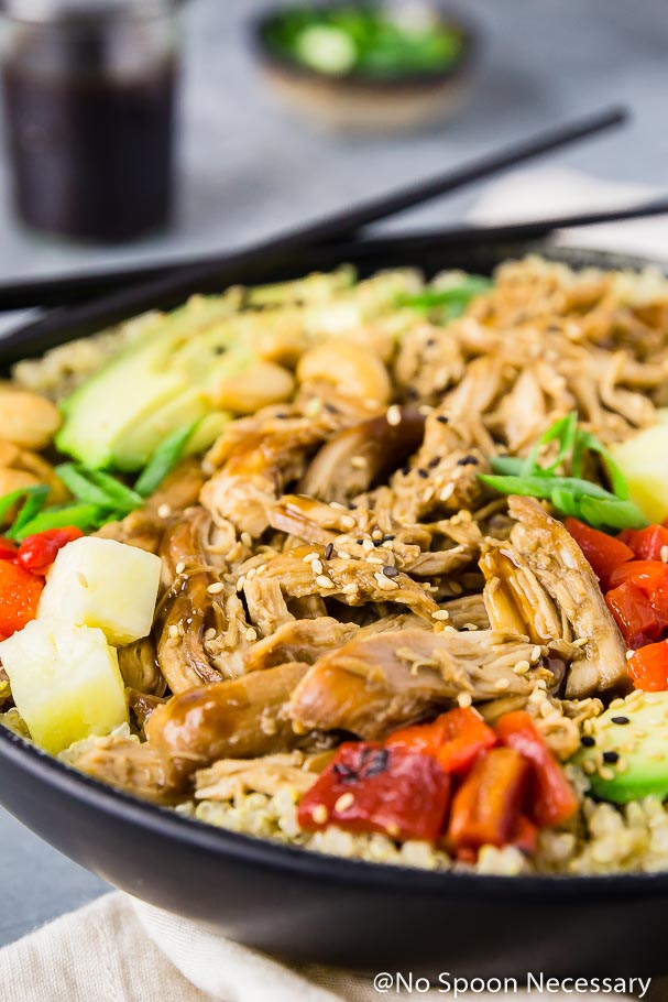 Angled, up-close shot of a Slow Cooker Chicken Teriyaki Quinoa Bowl with black chop sticks balancing on the bowl and sliced green onions and a jar of teriyaki sauce blurred in the background
