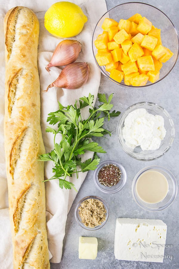 All the ingredients needed to make Caramelized Butternut Squash Crostini neatly organized with a neutral linen on a gray surface.