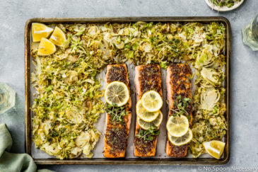 Overhead shot of Baked Honey Dijon Salmon with Brussels Sprouts on a sheet pan with a light green linen, glasses of wine and ramekin of microgreens surrounding the pan.