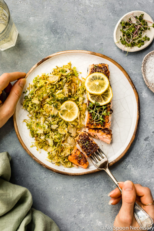 Overhead shot of Baked Honey Dijon Salmon with Brussels Sprouts on a plate with a hand holding the plate and another hand holding the fork cutting into the salmon; with a light green linen, glass of wine and ramekin of microgreens surrounding the plate.