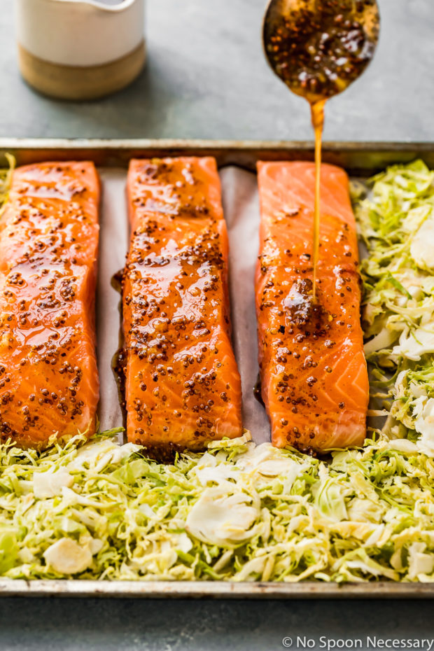 Angled shot of honey dijon mixture being poured over filets of salmon on a sheet pan with brussels sprouts surrounding the salmon - photo of step 4 of the Baked Honey Dijon Salmon with Brussels Sprouts recipe.