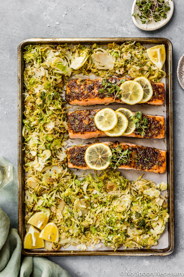 Overhead shot of Baked Honey Dijon Salmon with Brussels Sprouts on a sheet pan with a light green linen, glass of wine and ramekin of microgreens surrounding the pan.