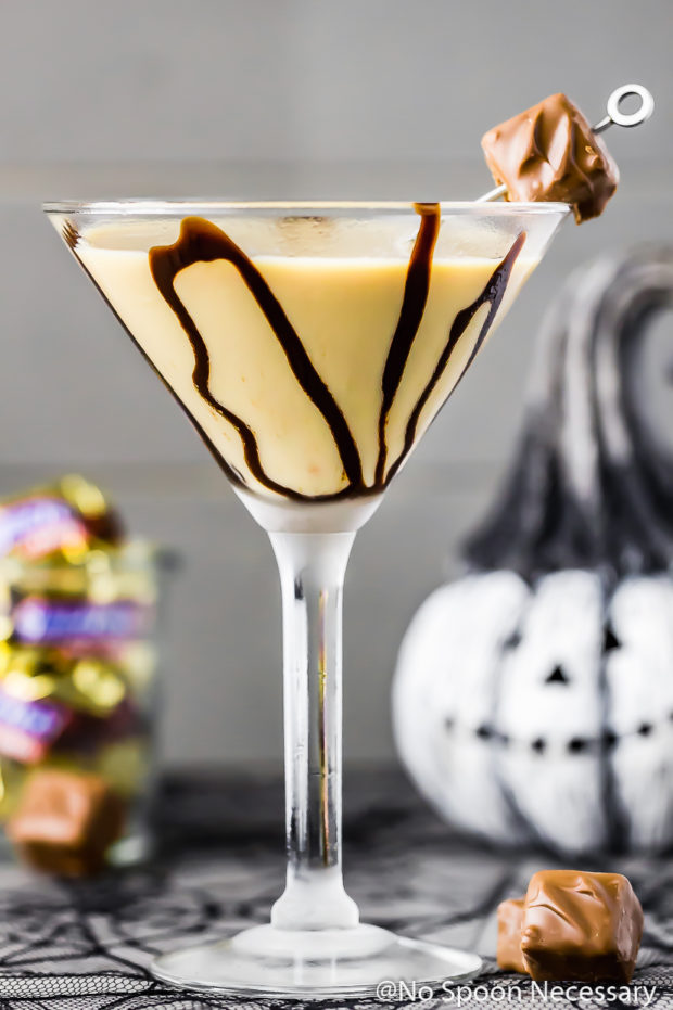 Straight on shot of a Snickers Chocolate Martini garnished with chocolate syrup and a mini snickers with a jar of snickers candy and a small jack-o-lantern blurred in the background.