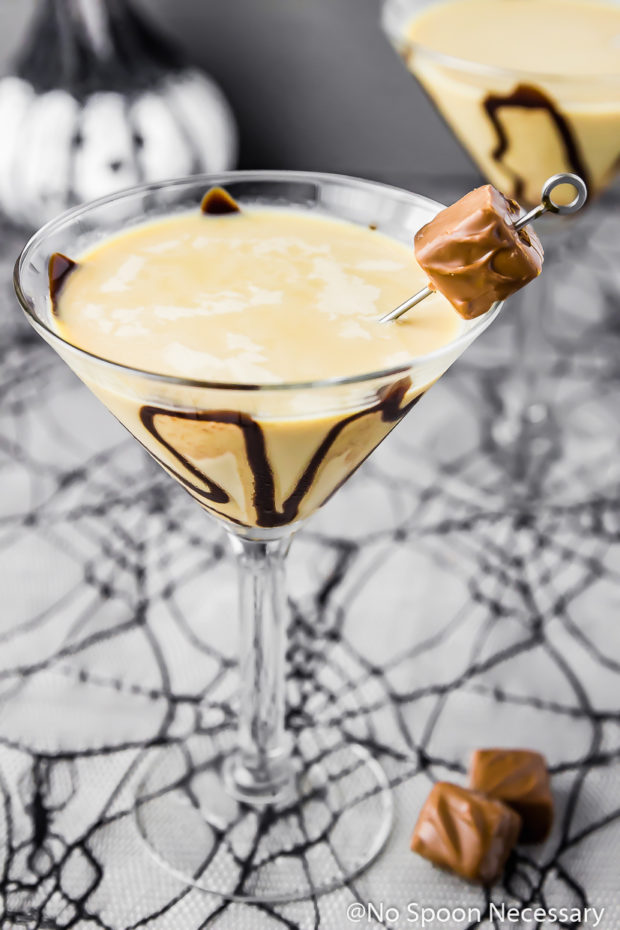Angled shot of a Snickers Chocolate Martini garnished with chocolate syrup and a mini snickers with an additional Snickertini and a small jack-o-lantern blurred in the background.