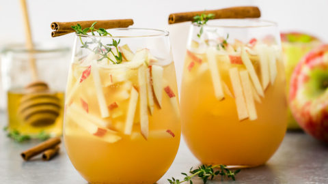 Straight on, landscape shot of 2 clear stemless wine glasses filled with Apple and GIn Autumn Cocktail garnished with matchstick cut apples, fresh thyme sprigs and cinnamon sticks; with a small clear glass of honey and a honey stick blurred in the background.