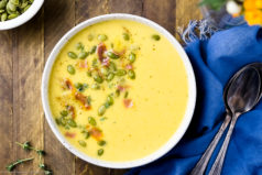 Overhead, landscape photo of a bowl of Cheddar Cheese Apple Soup garnished with pumpkin seeds and crispy bacon with a blue linen, spoons and orange flowers in a vase surrounding the bowl.