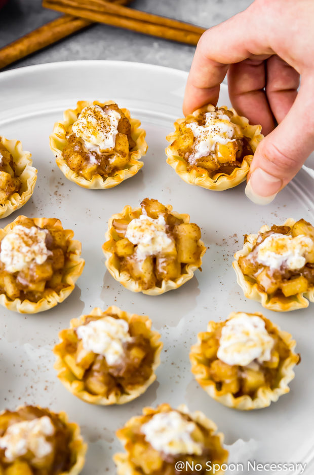 45 degree angle shot of Easy Apple Pie Bites topped with whipped cream and salted caramel sauce on a gray plate with a hand grabbing one of the bites off of the plate.