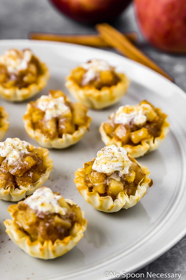 45 degree angle shot of Easy Apple Pie Bites topped with whipped cream and salted caramel sauce on a gray plate with cinnamon sticks and two apple blurred in the background.