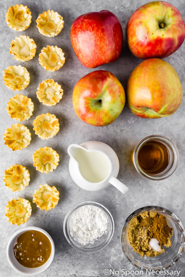 Overhead shot of all the ingredients needed to make easy Apple Pie Bites neatly organized on a gray surface.