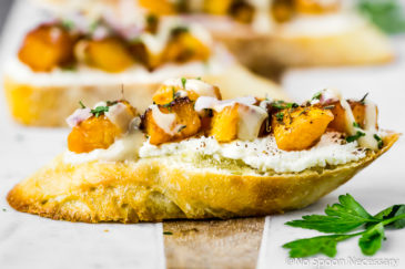 Straight on shot of a Caramelized Butternut Squash Crostini topped with whipped Feta, za'atar and tahini on a marble and wood bread board with more crostini blurred in the background.