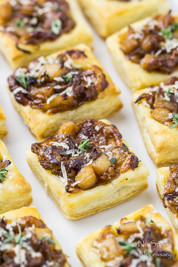 Angled, up close shot of a white platter filled with Caramelized Onion Pear Tarts garnished with fresh thyme with the focus on one individual tart.