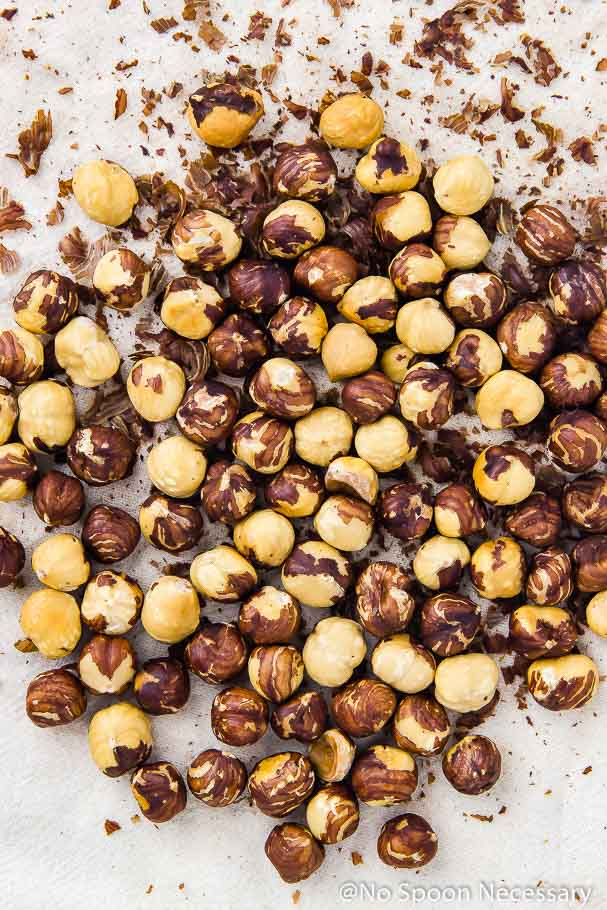 Overhead shot of a pile of partially peeled roasted hazelnuts on a tea towel