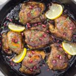 Overhead shot of Skillet Honey Pomegranate Chicken Thighs in a cast iron skillet garnished with lemon wedges and pomegranate arils with a light neutral linen under the skillet.