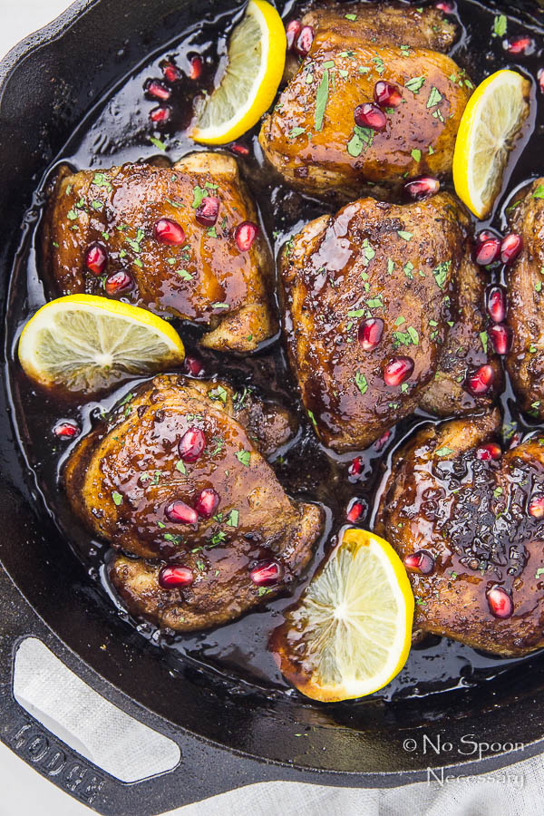 Overhead shot of Skillet Honey Pomegranate Chicken Thighs in a cast iron skillet with lemon wedges and pomegranate arils.