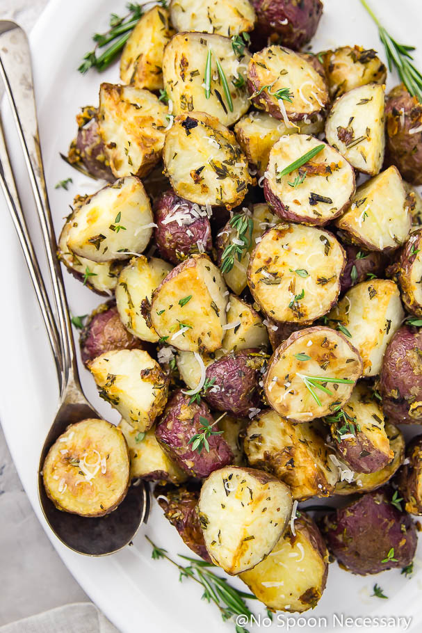 Overhead, up-close shot of Overhead shot of Asiago, Garlic & Herb Roasted Red Potatoes on a white platter with serving spoons tucked under the potatoes