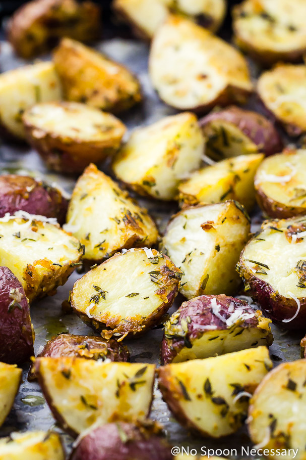 Angled shot of Overhead shot of Asiago, Garlic & Herb Roasted Red Potatoes on a parchment paper lined sheet pan
