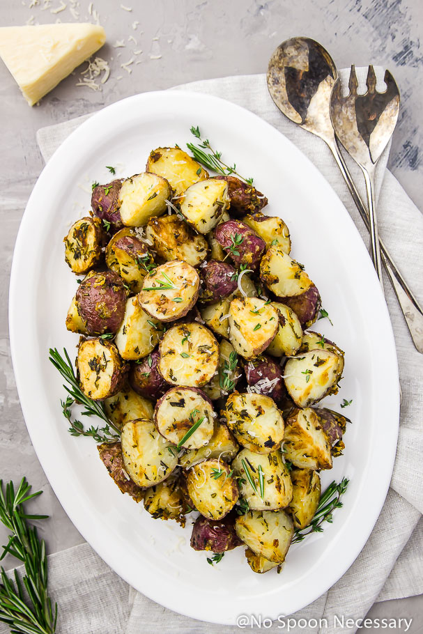 Overhead shot of Asiago, Garlic & Herb Roasted Red Potatoes on a white platter with serving spoons, a small block of parmesan and fresh herbs in the corner