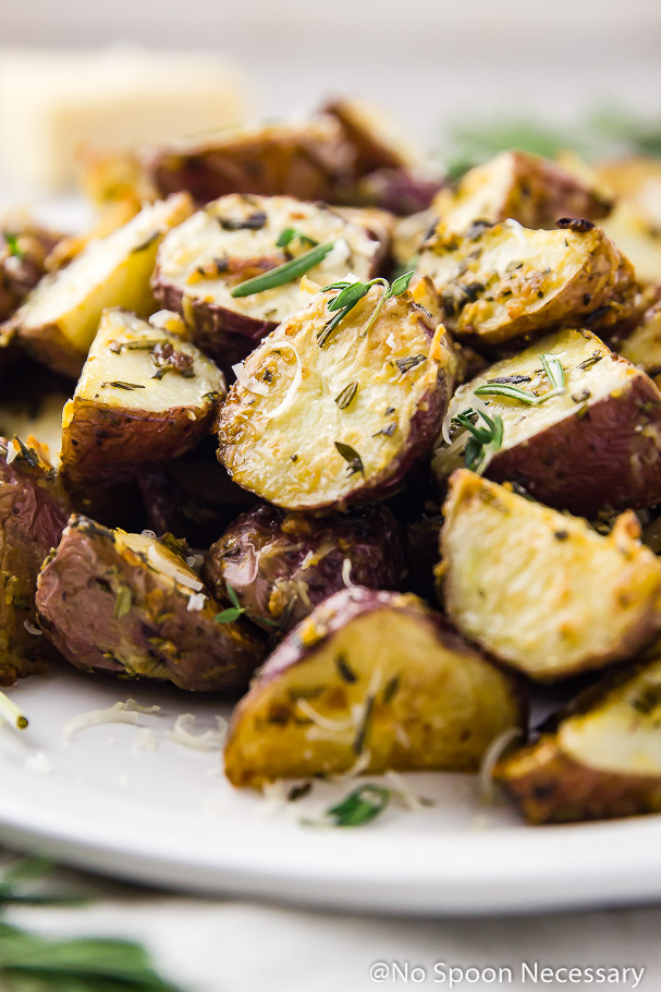 Angled, close-up shot of Asiago, Garlic & Herb Roasted Red Potatoes on a white platter garnished with fresh herbs and grated parmesan