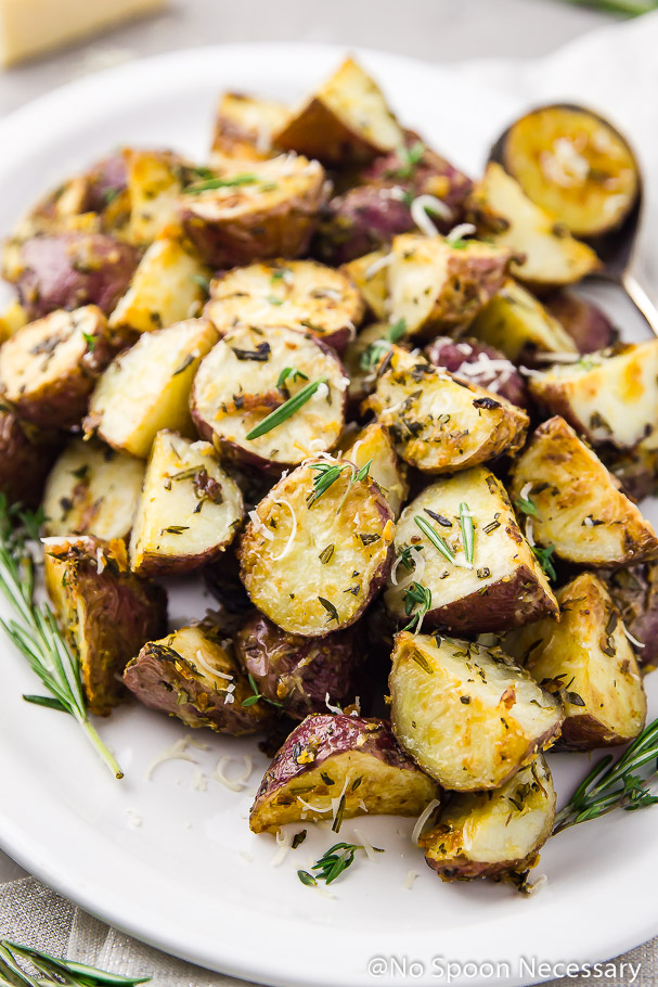 Angled shot of Asiago, Garlic & Herb Roasted Red Potatoes on a white platter with serving spoons tucked under the potatoes