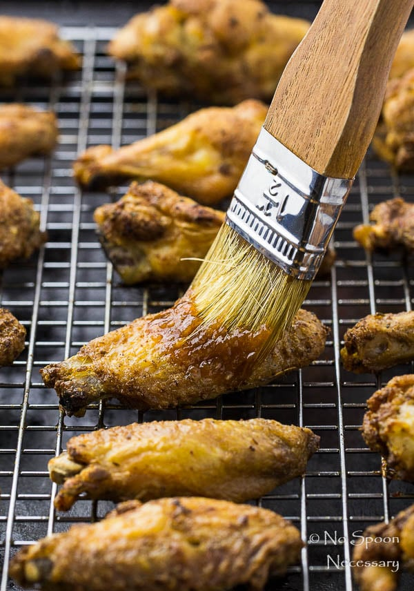 45 degree angle shot of Crispy Baked Cajun Chicken Wings on a wire rack lined baking sheet with a large grill brush applying glaze to the wings.