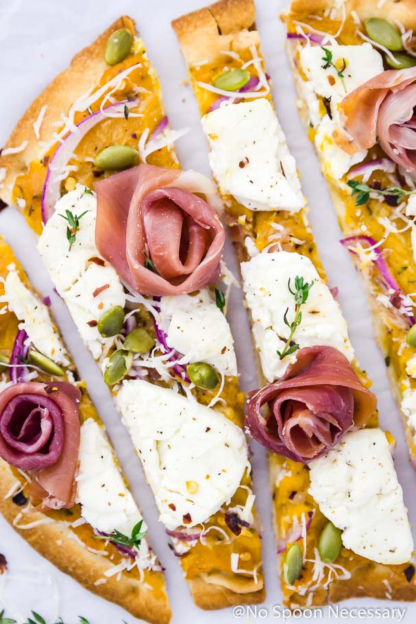 Overhead, up-close shot of a few long vertical slices of Butternut Squash Flatbread Pizza with Goat Cheese, Prosciutto & Pumpkin Seeds on a crinkled piece of parchment paper