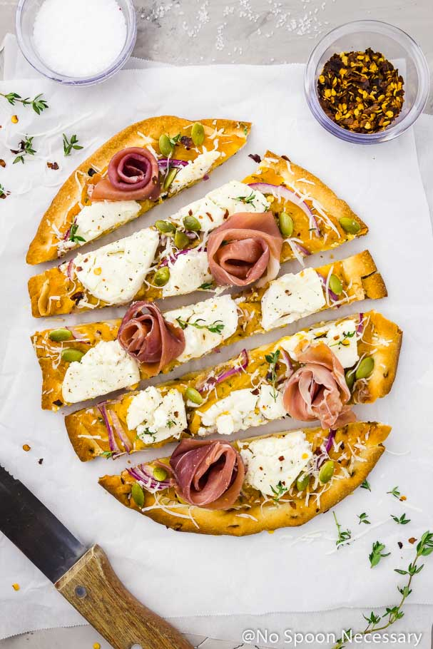 Overhead shot of Butternut Squash Flatbread Pizza with Goat Cheese, Prosciutto & Pumpkin Seeds cut into long horizontal slices on a crinkled piece of parchment paper with a wood handled steak knife, fresh thyme, ramekin of salt and ramekin of red pepper flakes surrounding the pizza