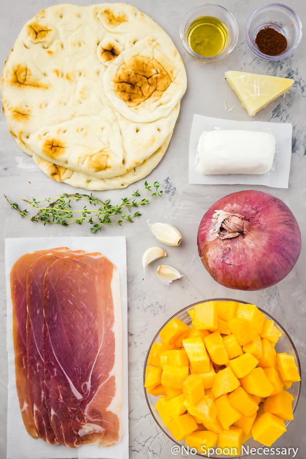 All the ingredients to make Butternut Squash Flatbread pizza neatly laid out on a bluish-gray surface