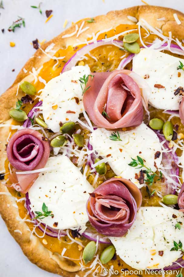Overhead, up-close shot of the prosciutto roses on a Butternut Squash Flatbread Pizza with Goat Cheese & Pumpkin Seeds