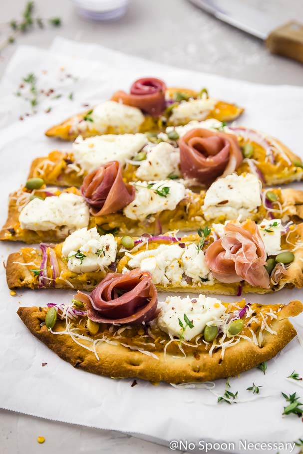 Angled shot of Butternut Squash Flatbread Pizza with Goat Cheese, Prosciutto & Pumpkin Seeds cut into long horizontal slices on a crinkled piece of parchment paper with a wood handled knife and small ramekin of salt blurred in the background