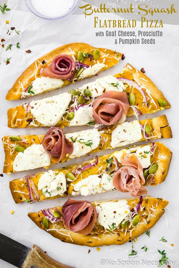 Butternut Squash Flatbread Pizza with Goat Cheese, Prosciutto & Pumpkin Seeds cut into long horizontal slices on a crinkled piece of parchment paper