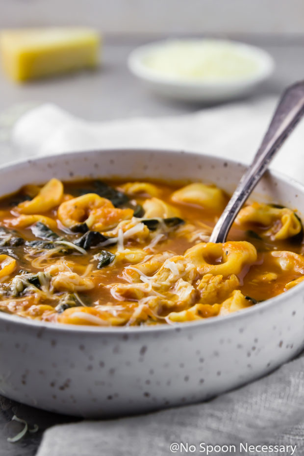 45 degree angle shot of a bowl of Easy Chicken, Spinach & Tortellini Tomato Soup on a gray surface and neutral colored linen with a spoon inserted into the bowl and a small bowl of shredded cheese and block of cheese blurred in the background.
